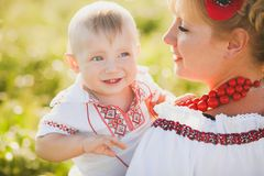 Portrait of ethnic ukrainian family. Wearing traditional white clothes. Young mother and little baby having fun outside at summer sunny wheat field. Vertical stock photo