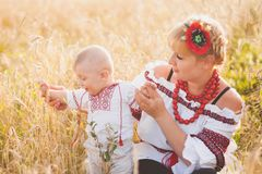 Portrait of ethnic ukrainian family. Wearing traditional white clothes. Young mother and little baby having fun outside at summer sunny wheat field. Vertical royalty free stock photography