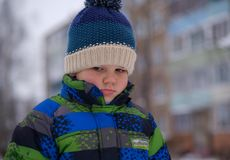 European boy with an emotion of resentment on the street in winter Royalty Free Stock Photos