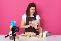 Portrait of European brunette attractive woman standing  over pink background in studio, looking attentively at tablet. Screen, searching for new recipe for her stock photos