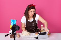 Portrait of European brunette woman cooking at kitchen, looking attentively at tablet screen, searching for new recipe on net,. Recording new video for her royalty free stock images