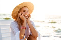 Portrait of european cheerful woman 20s in straw hat smiling, while sitting in lounge chair at seaside during summer morning. Portrait of european cheerful woman royalty free stock photos