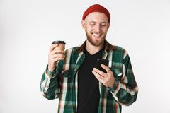 Portrait of european guy wearing plaid shirt holding paper cup with coffee and using mobile phone, while standing isolated over. Portrait of european guy wearing royalty free stock photography