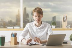 Portrait of european guy in office. Portrait of european guy working on project at modern desk with laptop, paperwork, supplies, coffee cup and other items Stock Photo