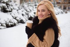 Portrait of european style fashionable woman drinking coffee in winter park. royalty free stock image