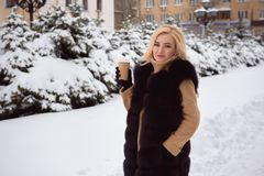 Portrait of european style fashionable woman drinking coffee in the winter park. stock photography