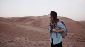 Portrait of European woman in desert. Slow motion. Young girl walks in desert canyon. Life difficulties and trials. Portrait of European woman in desert. Slow stock video