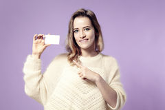 Portrait of european young smiling business woman holding credit card. isolated on violet background Royalty Free Stock Images