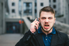 Portrait of an evil businessman who shouts to mobile phone against the backdrop of modern urban landscape.  Stock Photography