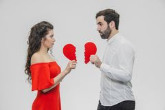 Portrait of an Excessive Couple. Conducting two parts of the heart paper. Isolated on a white background. Woman dressed in red men dress in white shirt stock image