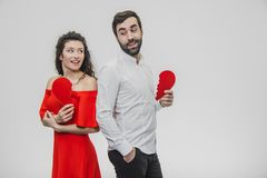 Portrait of an Excessive Couple. Conducting two parts of the heart paper. Isolated on a white background. Woman dressed in red men dress in white shirt royalty free stock images