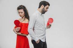 Portrait of an Excessive Couple. Conducting two parts of the heart paper. Isolated on a white background. Woman dressed in red men dress in white shirt royalty free stock photos
