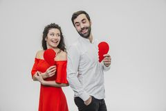 Portrait of an Excessive Couple. Conducting two parts of the heart paper. Isolated on a white background. Woman dressed in red men dress in white shirt stock photography
