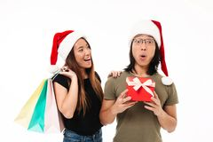 Portrait of an excited asian couple in christmas hats Royalty Free Stock Image