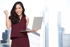 Portrait of an excited Asian woman holding laptop computer and celebrating success over building background, Raising arms with a. Look of happiness, Female royalty free stock images