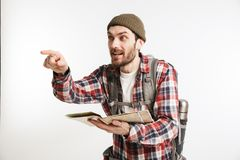 Portrait of an excited bearded man tourist in plaid shirt. Carrying backpack and holding a map  over white background Royalty Free Stock Photography