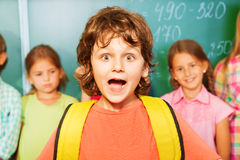 Portrait of excited boy with bag near chalkboard Royalty Free Stock Images