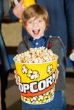 Portrait Of Excited Boy Offering Popcorn Bucket At Stock Images