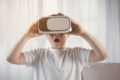 Surprised kid watching video on virtual reality headset stock photos