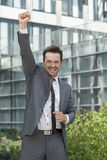 Portrait of excited businessman with arm raised celebrating success outside office building Stock Photography