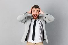 Portrait of an excited businessman dressed in suit. Covering his ears and screaming isolated over gray background Stock Photo