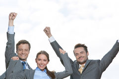 Portrait of excited businesspeople with arms raised on terrace against sky Royalty Free Stock Photos