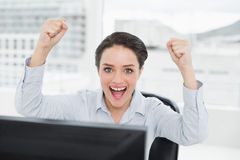 Portrait of an excited businesswoman clenching fists in office Royalty Free Stock Photo