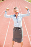 Portrait of excited businesswoman standing on the running track Royalty Free Stock Images