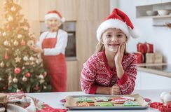 Happy family celebrating holiday with sweet traditional pastry. Portrait of excited child standing in kitchen and home and smiling. Holiday colorful cookies are Royalty Free Stock Photo