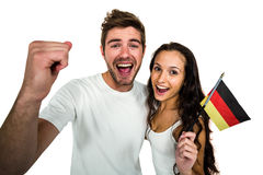 Portrait of excited couple holding German flag Stock Photo