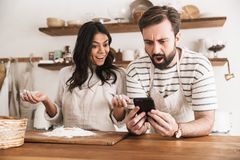 Portrait of excited couple reading recipe while cooking pastry with flour and eggs in kitchen at home. Portrait of excited couple men and women 30s wearing stock image