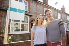 Portrait Of Excited Couple Standing Outside New Home With Sold Sign stock photos