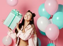 Portrait of an excited cute girl in jaket holding present box isolated over pink background royalty free stock image