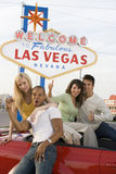 Portrait Of Excited Friends With Car. And 'Welcome To Las Vegas' sign in the background Stock Photo