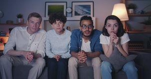 Portrait of excited friends watching tv at night looking at camera talking stock video