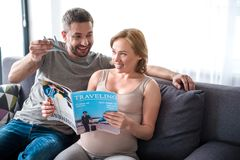 Happy pregnant lady reading traveling journal with husband. Portrait of excited future parents are dreaming of travel. Man is playing with little aircraft toy stock images