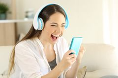 Excited girl finding offers online listening to music. Portrait of an excited girl finding offers online in a smartphone and listening to music at home Stock Photos
