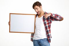 Portrait of an excited guy pointing finger at blank board Royalty Free Stock Photography