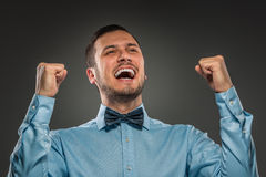 Portrait excited, happy man, arms up fists pumped celebrating su. Closeup portrait of excited, energetic, happy, man in blue shirt and butterfly tie winning Stock Photo