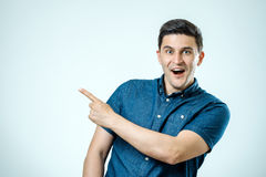 Portrait of an excited happy man pointing finger away at copy sp stock photo