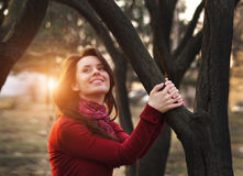 Portrait of an excited lady smiling and warming in sunset light in a city park.  Royalty Free Stock Photo