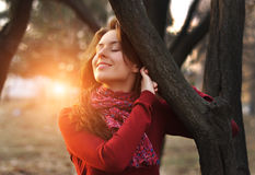 Portrait of an excited lady smiling and warming in sunset light in a city park.  Stock Image