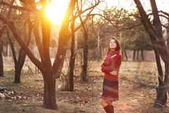 Portrait of an excited lady smiling and warming in sunset light in a city park.  Stock Photo