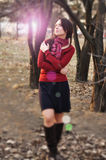 Portrait of an excited lady smiling and warming in sunset light in a city park.  Royalty Free Stock Photography