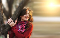 Portrait of an excited lady smiling and warming in sunset light in a city park Royalty Free Stock Photo