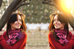 Portrait of an excited lady smiling and warming in sunset light in a city park.  Royalty Free Stock Images