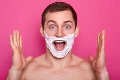 Portrait of excited man with foam on his face. Suprised guy isolated over rose background with shaving cream on cheeks. Male with. Naked shoulders, clasps hands stock photos