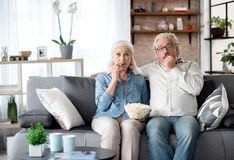 Senior man and woman viewing TV at home. Portrait of excited mature married couple watching television in living room. They are sitting on sofa and eating Stock Image