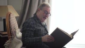 Portrait of excited old man watching photos in album. Positive senior Caucasian retiree recalling memories indoors