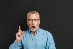 Portrait of excited retired man 60s with grey hair and beard in. Shirt shouting in surprise have idea and pointing index finger upward on copyspace isolated Stock Image